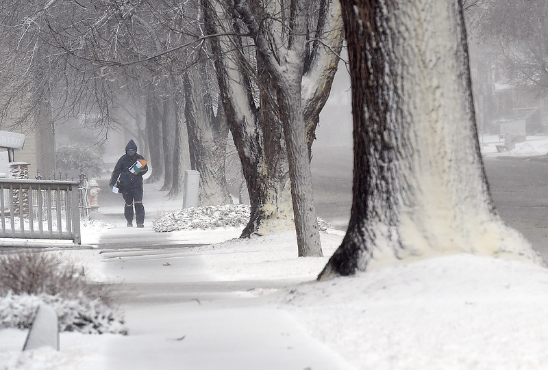 U.S. Postal carrier Kimberly Batson is all bundeld up as she delivers mail in blizzard conditions Wednesday, March 13, 2019, on the 900 block of Cleveland Avenue in downtown Loveland.   (Photo by Jenny Sparks/Loveland Reporter-Herald)