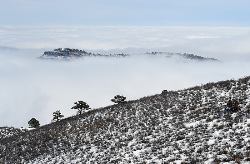 The top of a mountain near Flatiron Reservoir is visible through the fog Thursday, March 7, 2019, seen from County Road 18E west of Loveland. On a clear day all of Loveland, including the sugar factory, can be seen from this scenic outlook. (Photo by Jenny Sparks/Loveland Reporter-Herald)