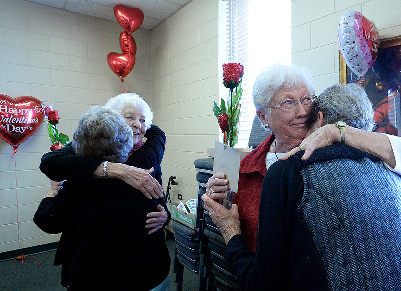 Long-time volunteer valentine stampers Joyce Boston, left, and Joan Williams, hug retiring fellow long-time stampers Delaney Phillips, left, and Janice Gibb during a luncheon to honor the Loveland Valentine Remailing Program stampers Wednesday, Feb. 20, 2019, at Trinity Lutheran Church in Loveland. King Soopers northern Colorado district provides food for the annual lunch and store managers serve the meal to the stampers to help thank them for their service to the community and honor them. (Photo by Jenny Sparks/Loveland Reporter-Herald)