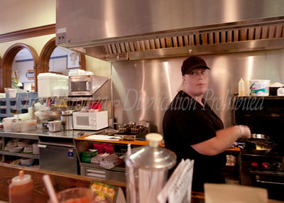 The cook with the golden touch at the soda fountain and lunch counter at The Corner Pharmacy in Leavenworth, Kansas.   This pharmacy has been at this location for over 130 years.  The present pharmacist and owner, Ron Booth bought the pharmacy in 1980 and restored the store with meticulous attention to detail and authenticity.  The food is as good as it gets and visiting this nostalgic store was a trip down memory lane for me.  I  hope to return again soon and try their signature, old time flavor hamburgers or hot dogs.  Photo #123