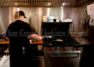 The cook at the lunch counter at The Corner Pharmacy doing what she does best.  The grill unit had  red knobs to adjust the heating surface - All the details were so complete in all areas of this nostalgic place.  Photo #125