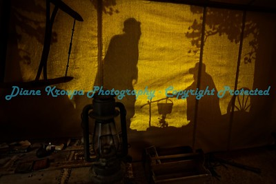 From inside miner's tent, shadows of prospectors sharing grub over a fire - Deadwood, SD.  Photo# 155