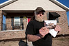 Man holds photo of his house that was destroyed in tornado