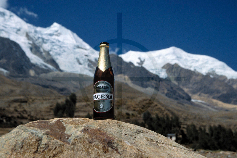 After action, satisfaction. Bottle of local beer displaying the mountain in the background, Illimani base camp, Cordillera Real, Bolivia