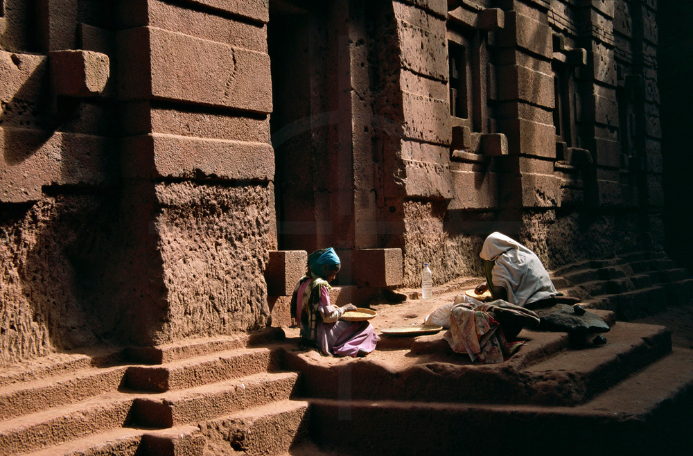 Mother and daughter sifting grains at an entrance of a rock-hewn church, Lalibela, Ethiopia