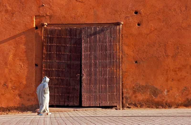 Man walking past a gate in the city walls of the medina of Marrakesh, Morocco