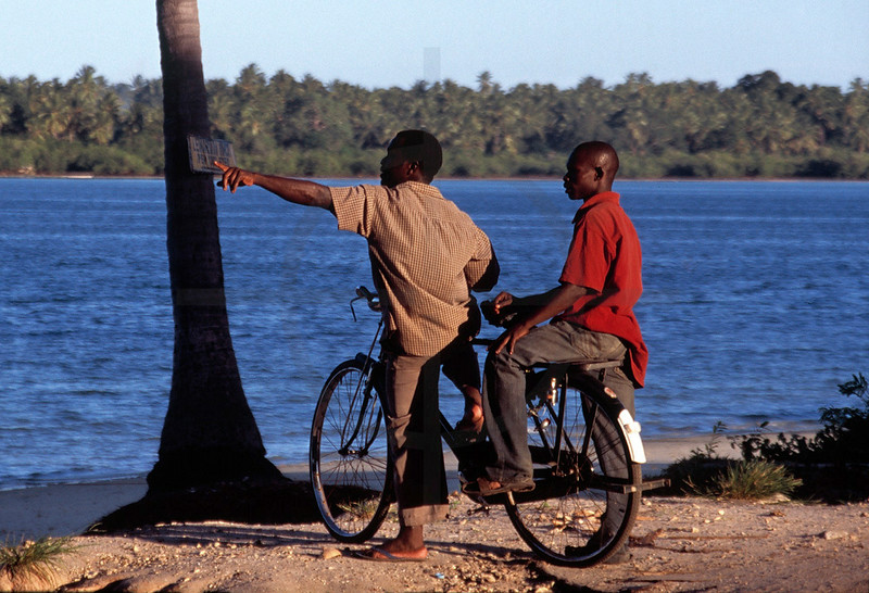 Tanzanians on a bicycle pointing, Mafia Island, Tanzania