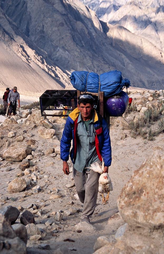 Porter with kitchen and live chicken leaving Paiju, Baltoro Glacier Trek, Karakoram Range, Baltistan, Pakistan