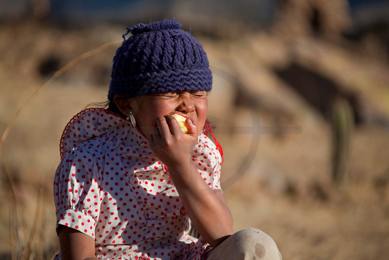 Native ethnic girl eating an apple,  Jatun Yampara, Chuquisaca, Bolivia