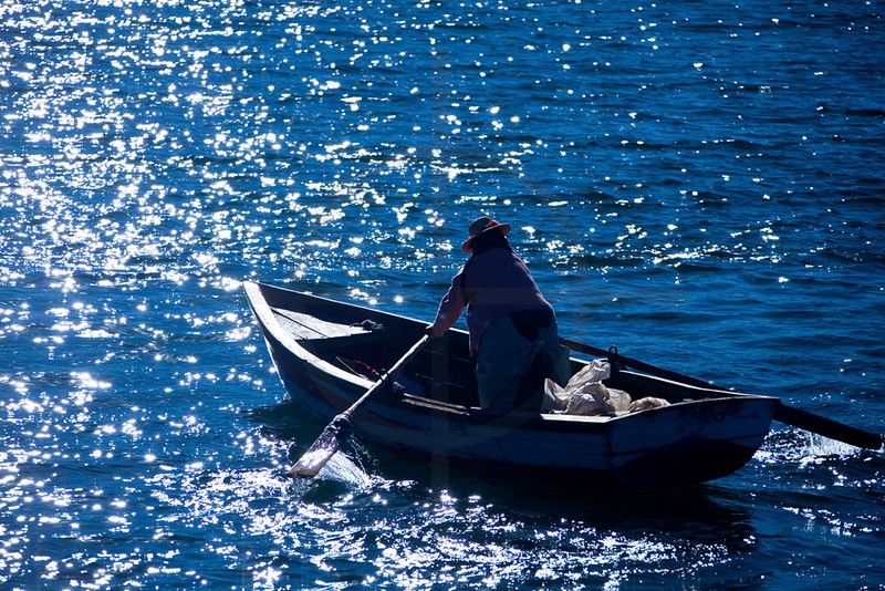 Local rowing on Lake Titicaca in late afternoon sun, Puno area, Peru
