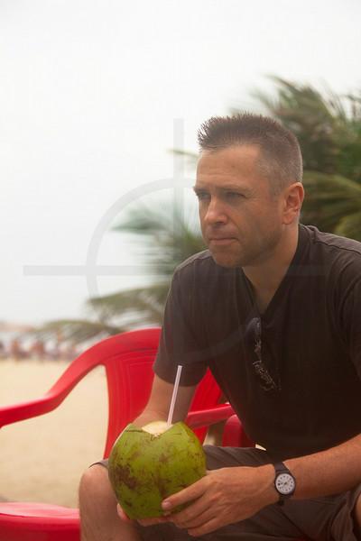 Man sitting with fresh coconut juice at Ipanema Beach, Rio de Janeiro, Brazil