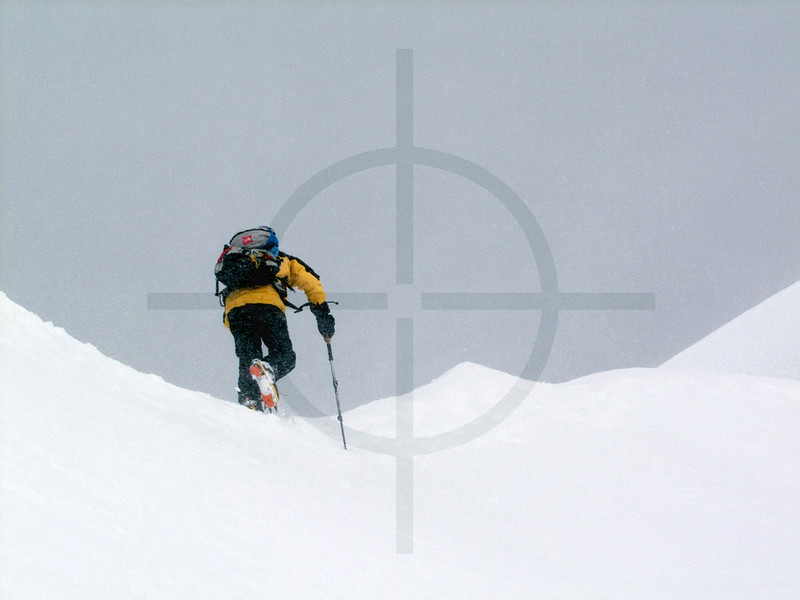 Climber on summit ridge of Pik Korzhenevskaya in snowy conditions, Pamir, Tajikistan