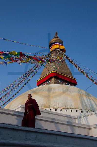 Buddhist monk performing a kora around the upper level of Boudhanath, Kathmandu, Nepal