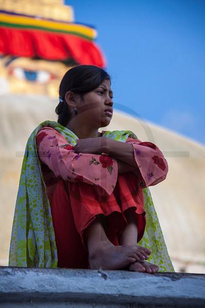 Nepali girl sitting and watching, upper level of Boudhanath Stupa, Kathmandu, Nepal