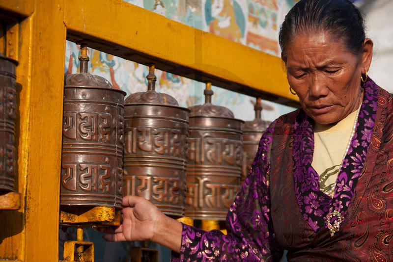 Buddhist woman spinning prayer wheels at Boudhanath, Kathmandu, Nepal
