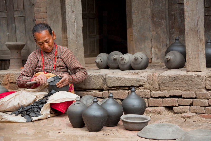 Potter carving the bottom of clay money boxes, Pottery Square, Bhaktapur, Kathmandu Valley, Nepal