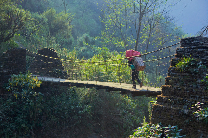 Porter crossing a footbridge over the Chomrong Khola, Annapurna Massif, Nepal
