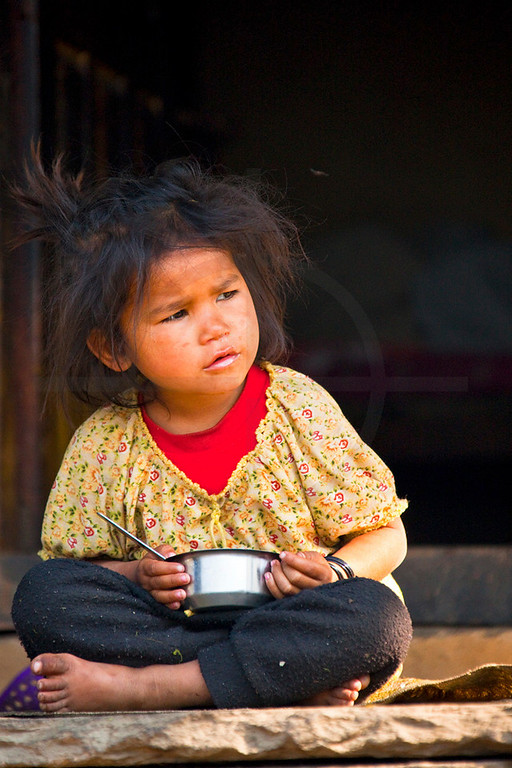Barefooted girl at breakfast wtaching what's happening, Tilche, Annapurna Massif, Nepal