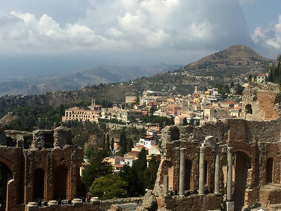 The Roman Amphitheater on top of the mountain with the town of Taormina in the background.