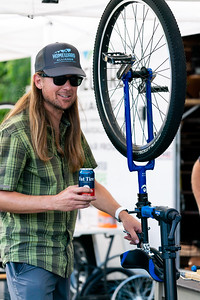 A volunteer mechanic works on a Unicycle before a unicycle cyclocross race.