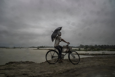 Dhemanji, Assam, India August,2014:   A man on his bicycle seen during a rain fall in Dhemanji district.   Series on early marriages in Assam, India for Al Jazeera America.       Photo:  Sami Siva