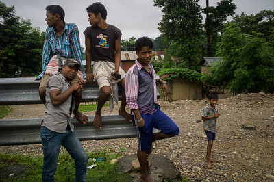 Dhemanji, Assam, India August,2014:   Young men (some already married) from  Simen Koi Bata village in Dhemanji District, wait for their bus to go to daily labour work in near by town.   Series on early marriages in Assam, India for Al Jazeera America.       Photo:  Sami Siva
