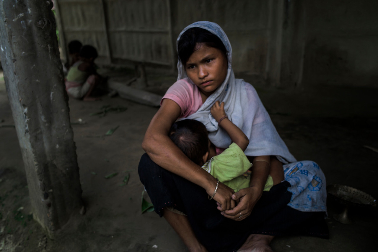 Dhemanji, Assam, India August,2014:   Debo Jani (16) was married at 12 and she has two kids.  She is seen with her younger child at her neighbours house in Guyekhanna village.   Series on early marriages in Assam, India for Al Jazeera America.       Photo:  Sami Siva