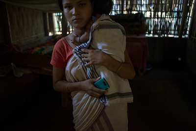 Dhemanji, Assam, India August,2014:   Janamani Das (14) married and has a one month old baby seen at her home in Simen Koi Bata village.  She lives alone as her husband works in southern state of Kerala.  Young girls communicate with boys using cell phones before their marriage.   Series on early marriages in Assam, India for Al Jazeera America.       Photo:  Sami Siva