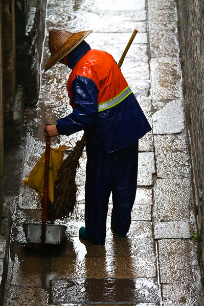 A worker cleans a walkway with a handmade broom in Xitang.