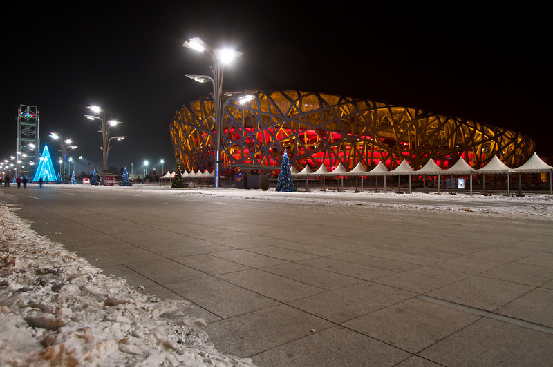 In an interesting dichotomy, the Beijing National Stadium (which hosted the 2008 summer Olympic Games) is found next to telltale signs of winter: snow and Christmas trees.