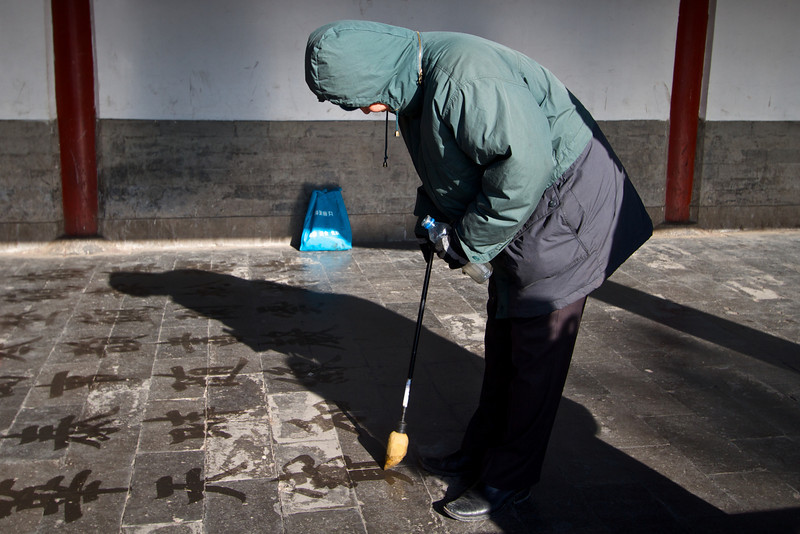 A man writes poems in the dust on the ground in the Temple of Heaven.