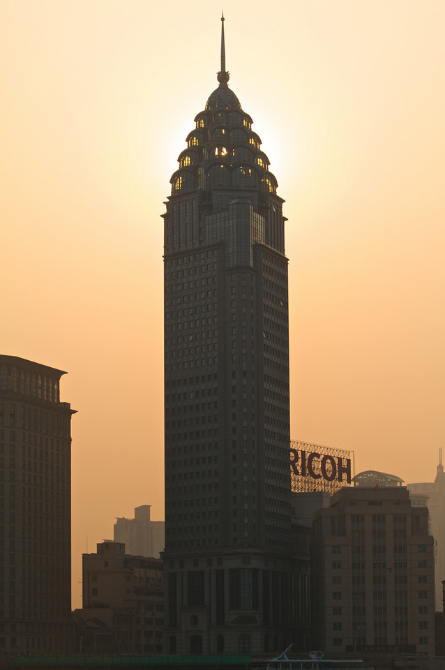 The sun hides behind a building in Puxi.