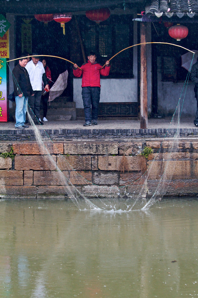 A fisherman attempts, fruitlessly, to catch some dinner in the canal waters in Xitang.