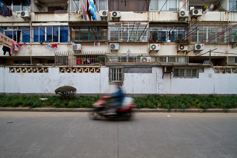 A man rides his moped along an alleyway in a residential area in Xuhui.