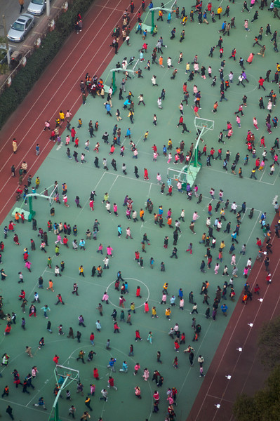 Children do their morning exercises by running in a snake-like formation. Students that didn't follow in line properly were immediately removed and forced to run along the side of the track.