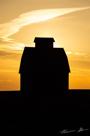 The sun sets behind a lone barn, the last remains of a farmstead dating back to 1889