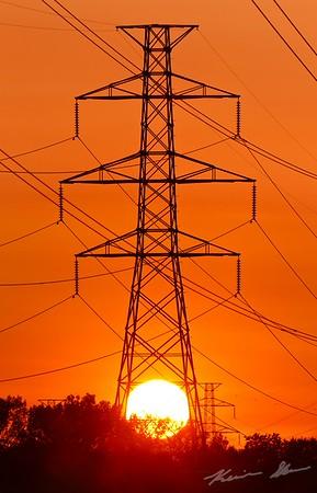 Blazing late summer sunset sets through power lines