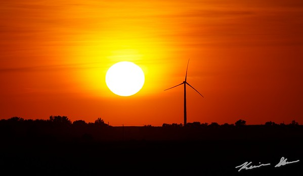 Summer sunset through a lone turbine