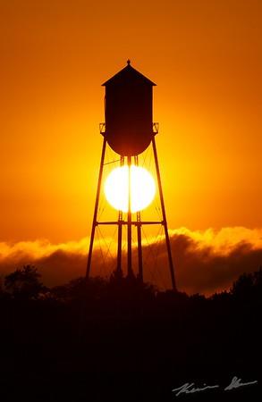 The Granger watertower carefully holds the setting sun