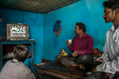 Chattisgarh, India, February 2015:   Kanhaiya Singh (R)  and Shivpal Bhagat (L) watch the results of Delhi elections in Singh's house.   Photographs for a story on land allocation for coal mines in Chattisgarh.  Modi's new government in the centre has relaxed the environmental regulations so the land can be allocated to both public and private sector companies easily.   Photo by Sami Siva for Al Jazeera America.