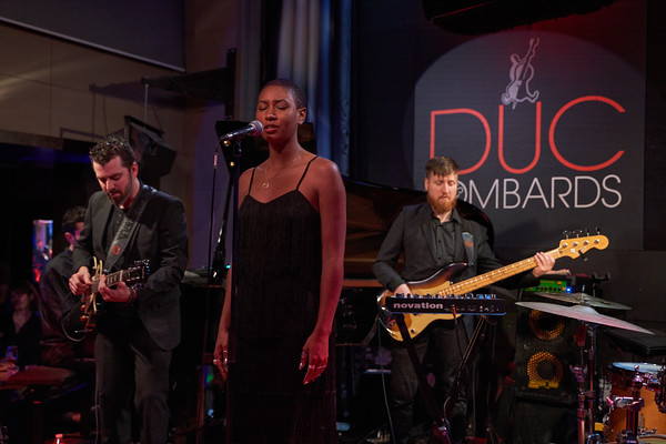 "Dominique Fils-Aimé show in Duc des Lombards, Paris, on December 2019, presenting her second album ""Stay tuned!"". On left, guitarist Etienne Miousse and in right bassist, Danny Trudeau and in right background Simon Denizart on piano."