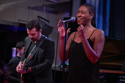 "Dominique Fils-Aimé show in Duc des Lombards, Paris, on December 2019, presenting her second album ""Stay tuned!"". In the center, guitarist Etienne Miousse and in background Simon Denizart on piano."