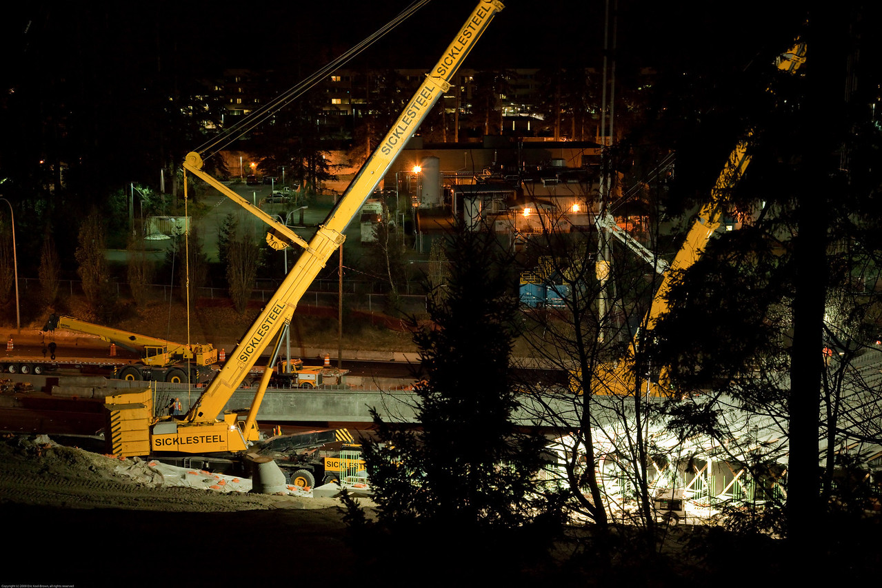 The near crane has been disconnected from the last girder and is swinging into position to hoist the next one.