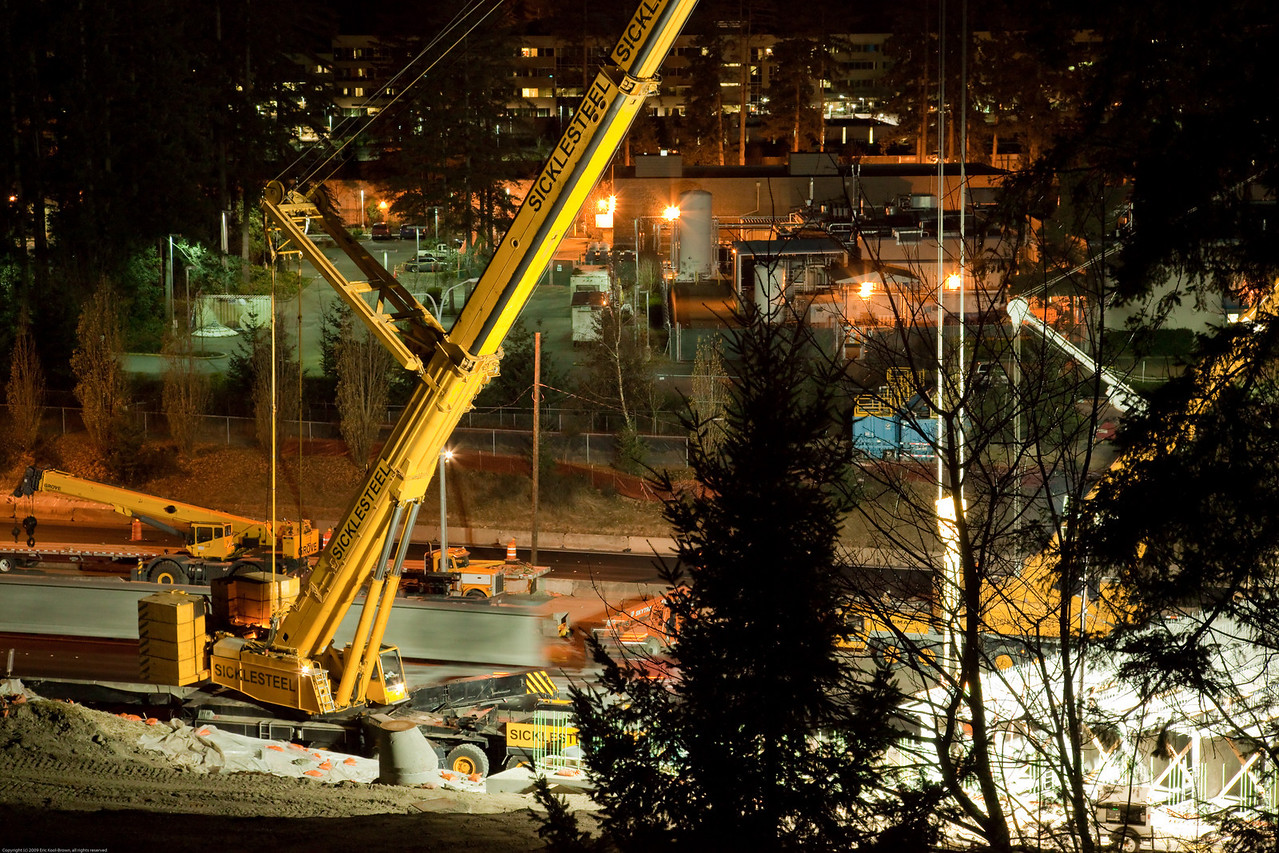 As the crew completes the placement of the prior girder, you can see the truck bringing the next one into position for lifting by the cranes.