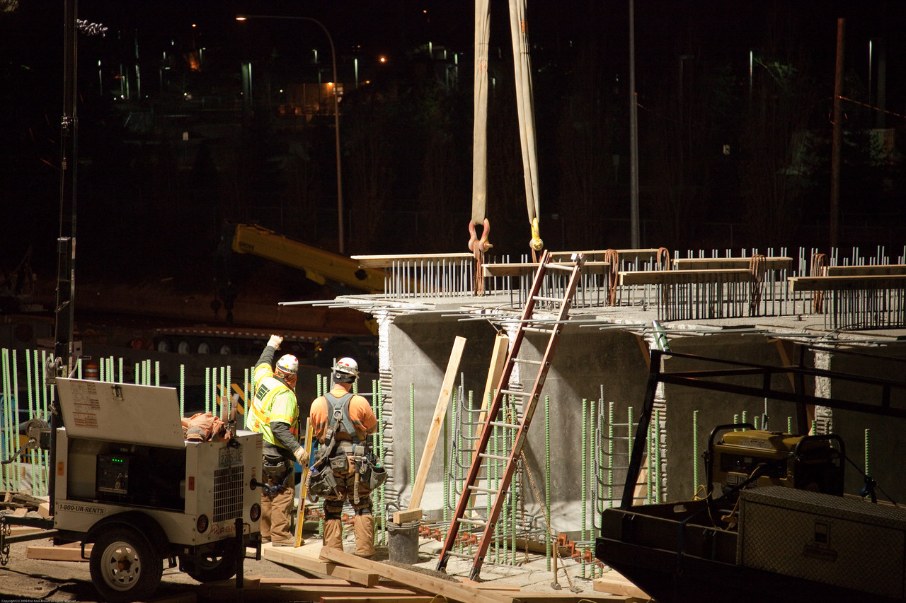 The carpenter on the left is giving the crane operator a hand signal to lower the girder the rest of the way.
