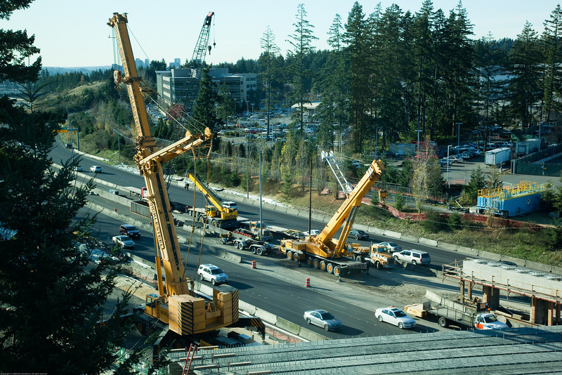 December 7, a dozen girders have been lifted into place over the weekend. The freeway is being closed from 11PM to 5AM so that the road-spanning pre-cast concrete beams can be placed by two huge cranes. These two Demag cranes have a combined lifting capacity of 950 tons.