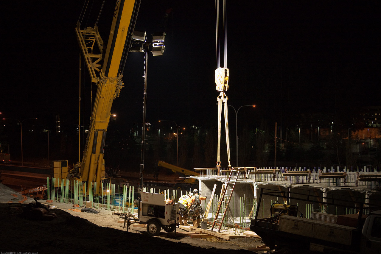 The carpenters measure to ensure that the girder is in the proper position.