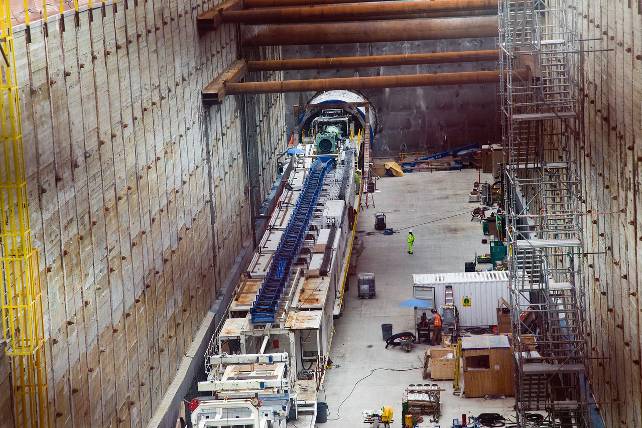 I discovered that if I zoomed in and then focused manually the screen was nearly invisible. That entire device on the left is the boring machine. All if it advances through the tunnel as the blade grinds away at the front. The tailings are carried away on a conveyor (the blue structure along the center; it doesn't have the belt installed yet). A separate conveyor will bring the concrete wall segments to the front. The borer has a mechanism that picks up the segments and puts them into their proper positions around the circumference of the tunnel.