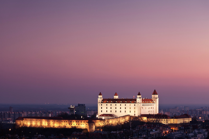 Bratislava Castle against a pink background at sunset.