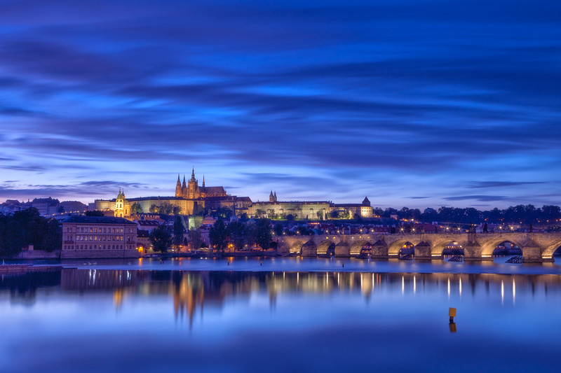This classic view of Prague includes Prague Castle and Charles Bridge at dusk. The exposure is extremely long so as to capture a proper reflection in the waters of the fast-moving Vltava.